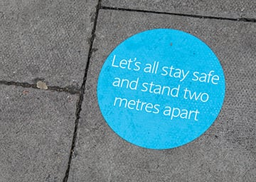 Sticker on floor reminding people to stand two metres apart