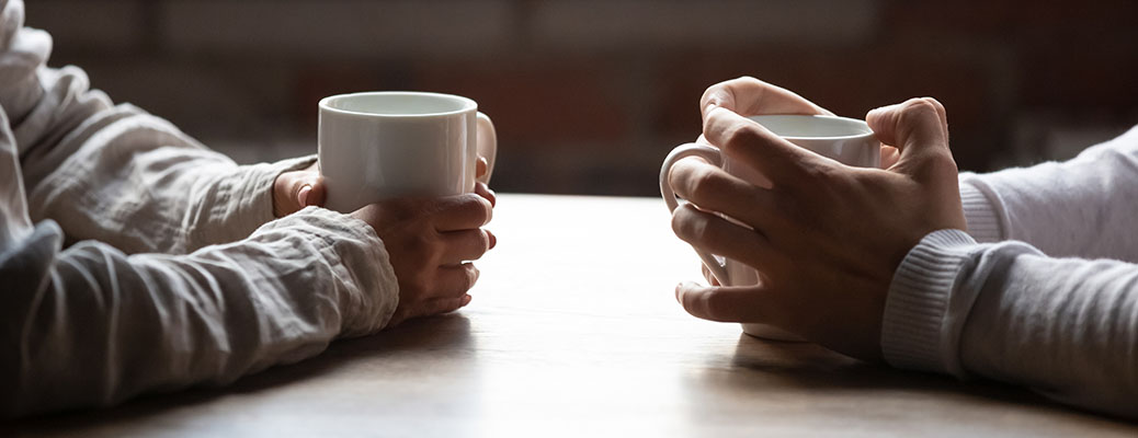 Two people holding cups with hot drinks